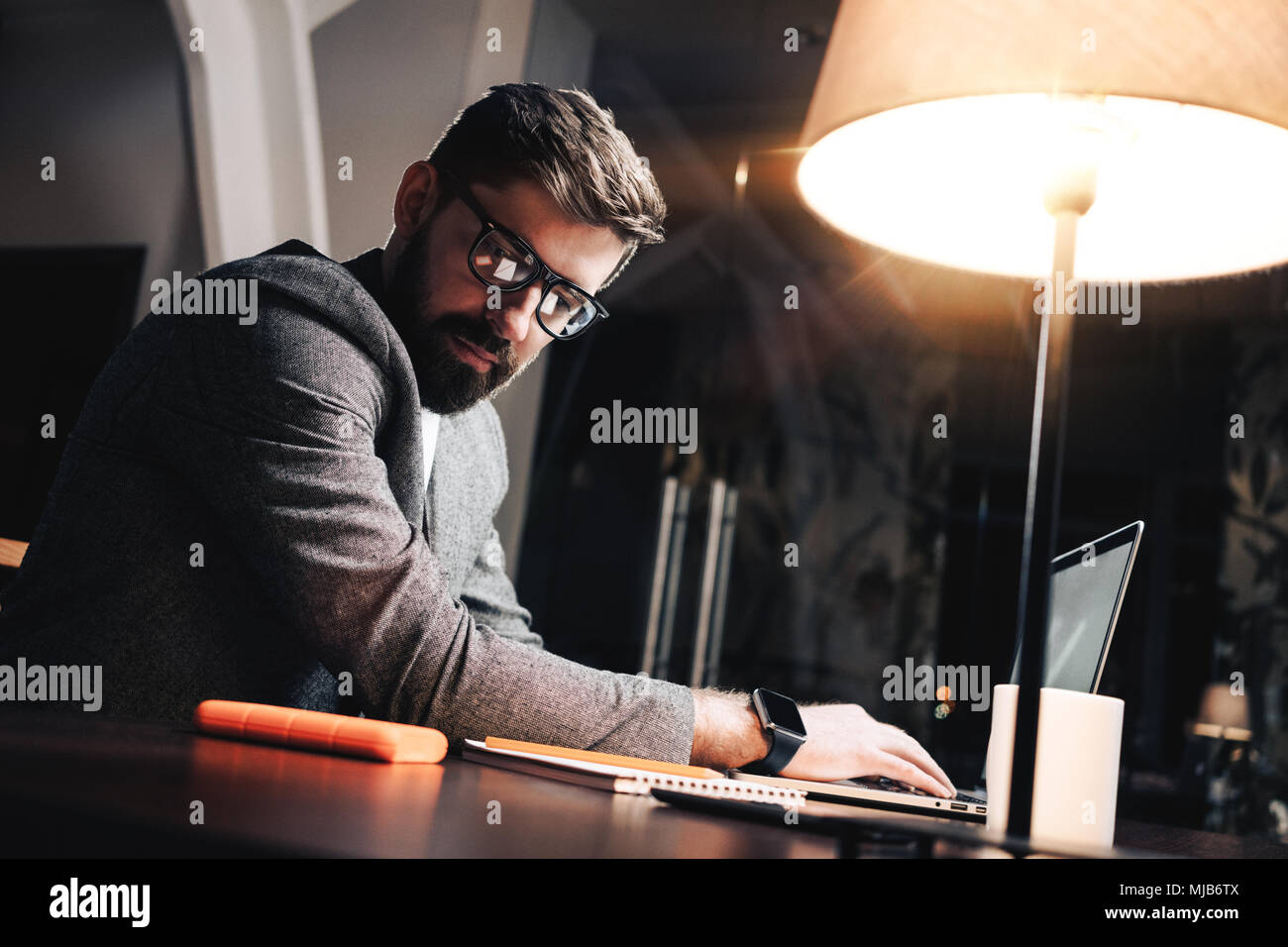 Young project manager looking on paper notepad and typing text on contemporary laptop. Bearded businessman working process in loft office at night. Fi - Stock Image