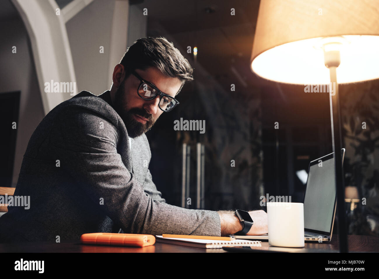 Young man working at night modern office. Blurred background. Bearded manager using laptop and paper notepad. Wearing office dress code and eye galsse - Stock Image