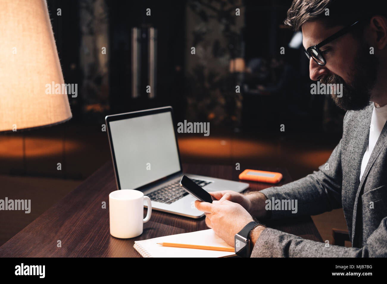 Smiling businessman with laptop and smartwatch using smartphone at night loft coworking studio. Bearded manager sits by the wooden table at modern off - Stock Image