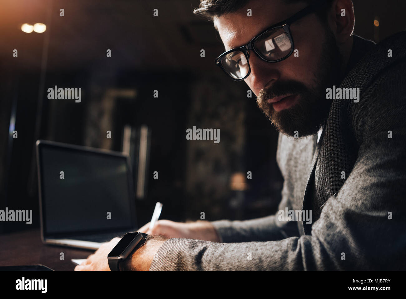 Close-up portrait of bearded businessman in glasses at night loft office. Creative manager working late evening over a new startup in coworking studio - Stock Image