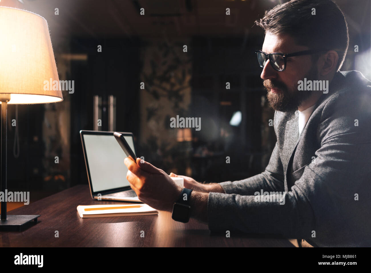 Bearded businessman wearing eye glasses and using pro computer at modern office at night. Coworker hold smartphone. Horizontal. Film effect - Stock Image