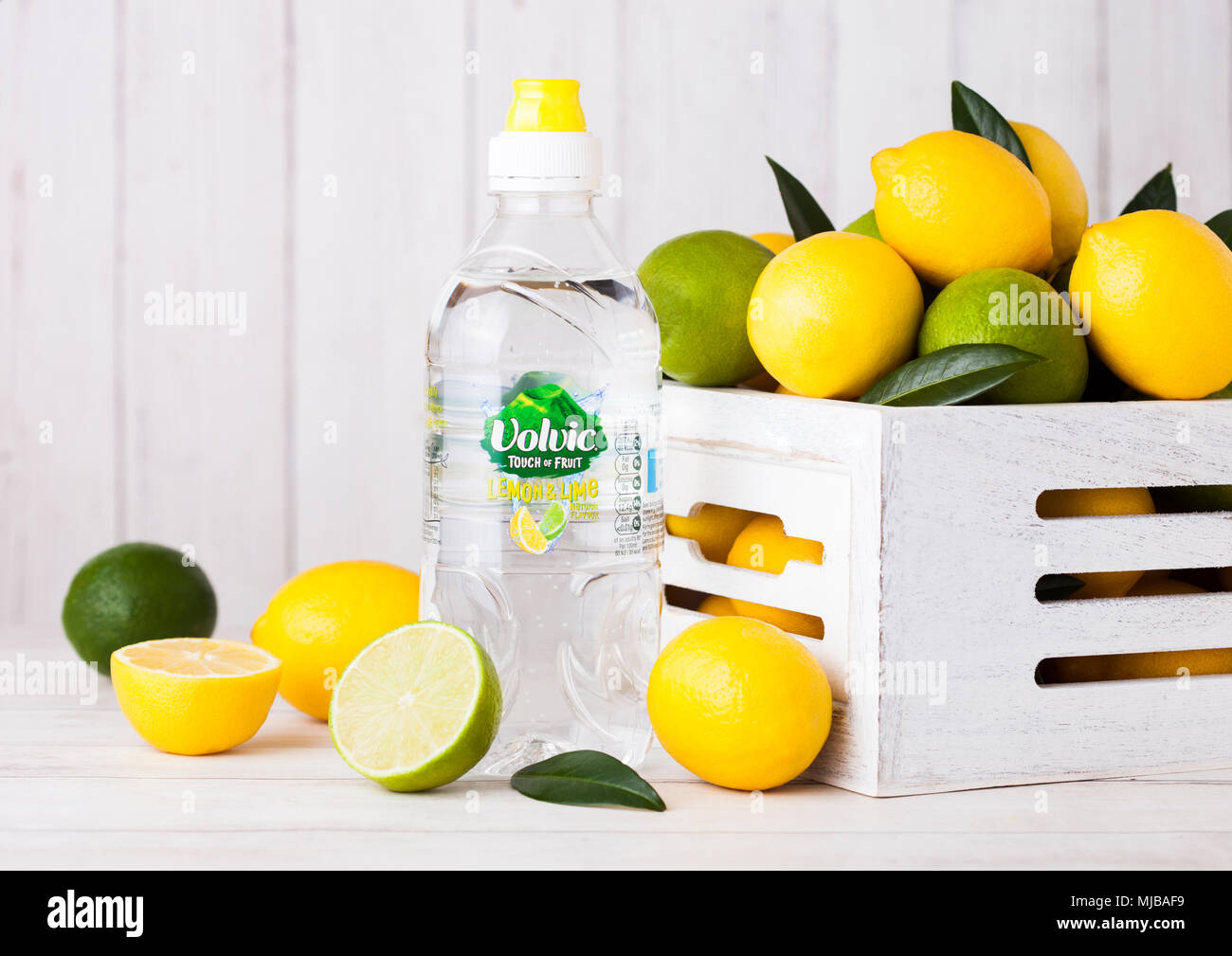 LONDON, UK - APRIL 12, 2017: Plastic bottle of Volvic still water on wooden background with lemons and limes in white wooden box. - Stock Image