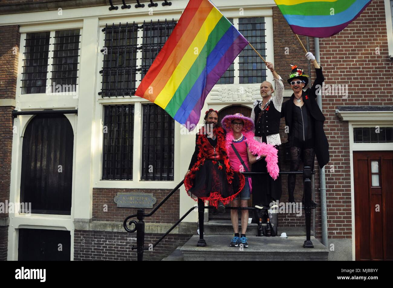 Amsterdam, Netherlands:  Four people in costumes standing on a balcony, waiving rainbow flags at the traditional Amsterdam gay pride event. - Stock Image
