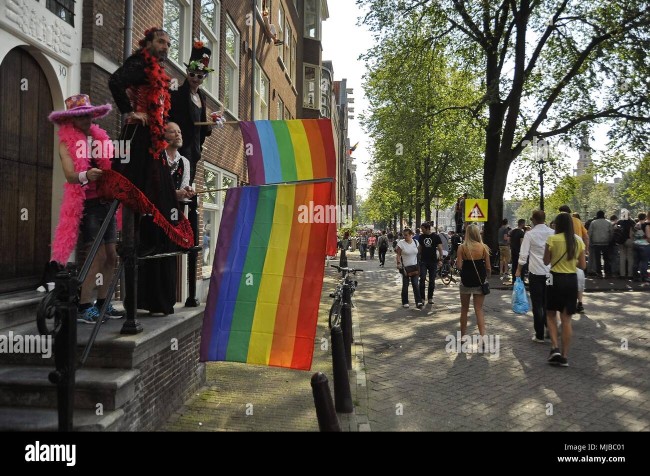 Amsterdam, Netherlands: Four men in costumes standing on a balcony, waiving rainbow flags to the crowd at the traditional Amsterdam gay pride event. Stock Photo