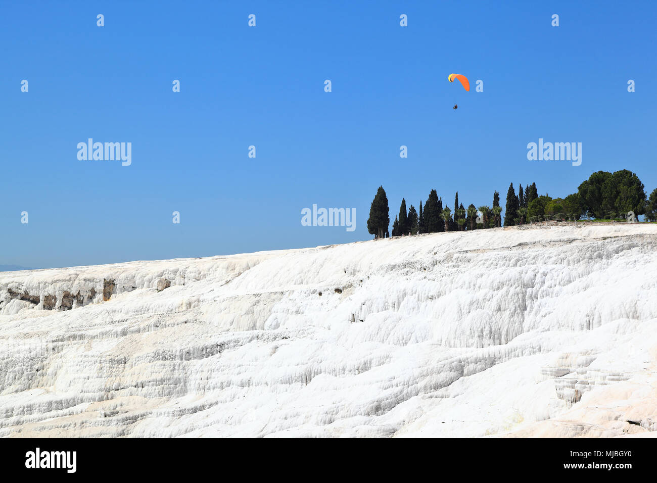 Pamukkale: Paraglider flying over the caclium deposits from the natural thermal springs. - Stock Image