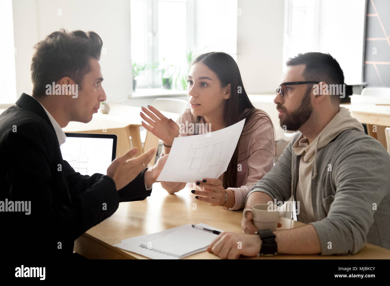 Angry couple disputing about mortgage or construction with lawye - Stock Image