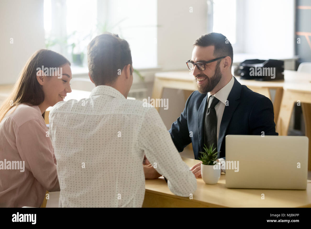 Friendly lawyer or financial advisor in suit consulting young co - Stock Image