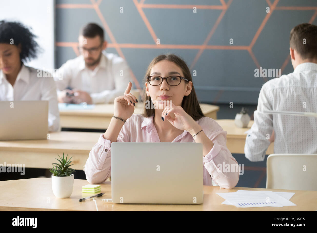 Thoughtful young woman thinking of new interesting idea at cowor - Stock Image
