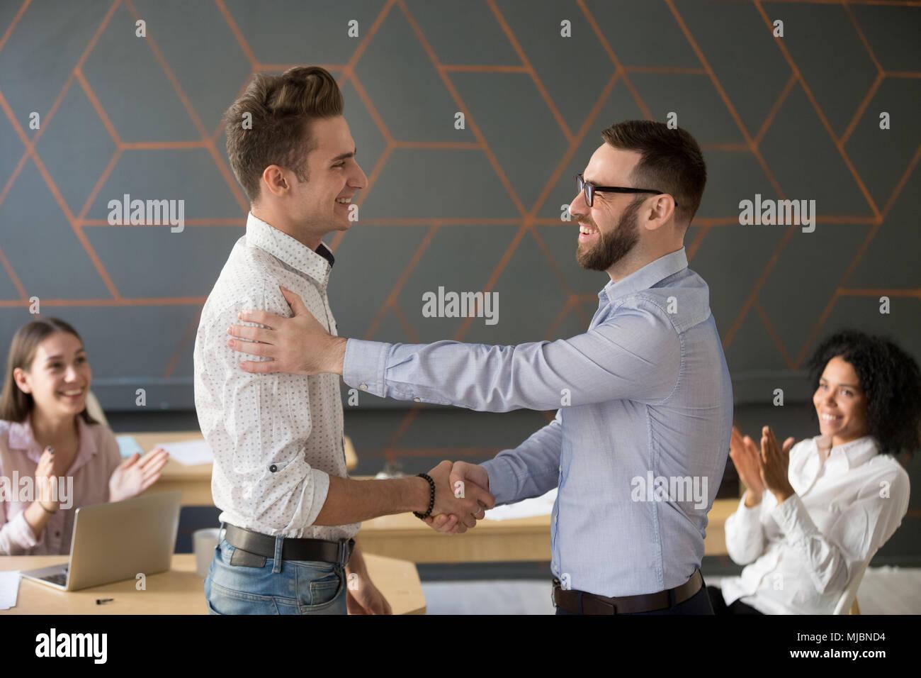 Team leader handshaking employee congratulating with professiona - Stock Image