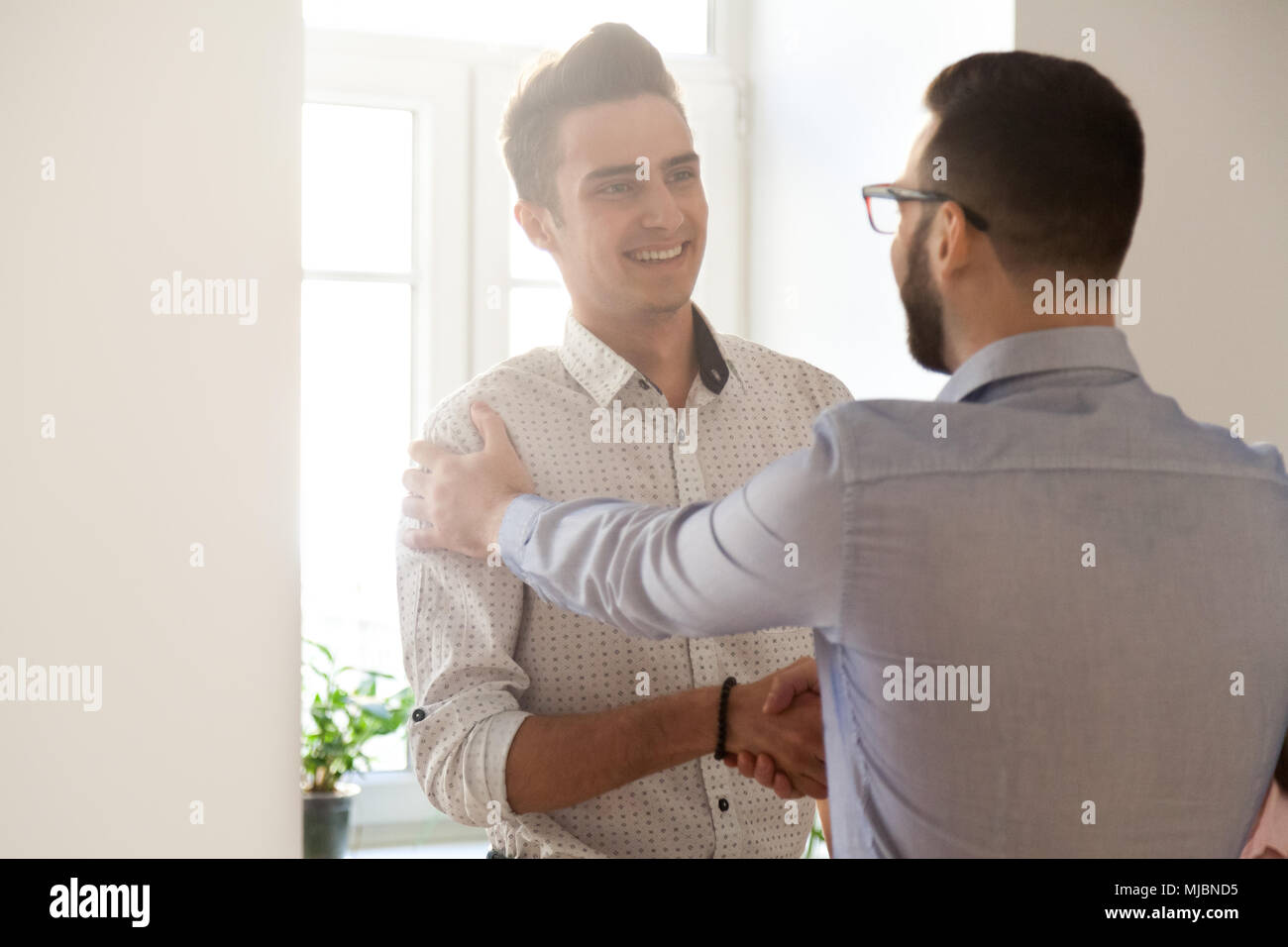 Grateful boss handshaking employee congratulating with job promo - Stock Image