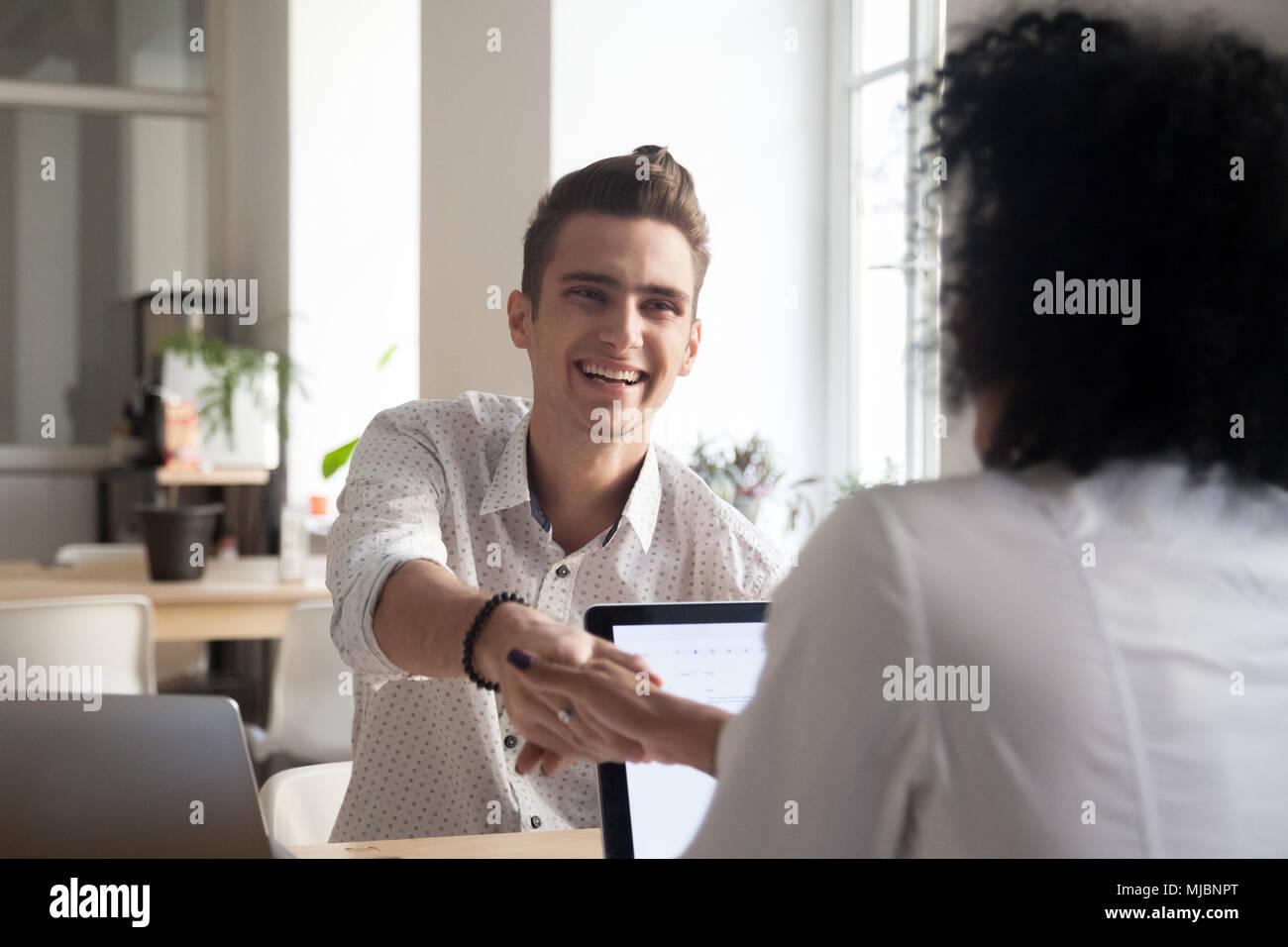Smiling millennial man handshaking african female coworker celeb - Stock Image