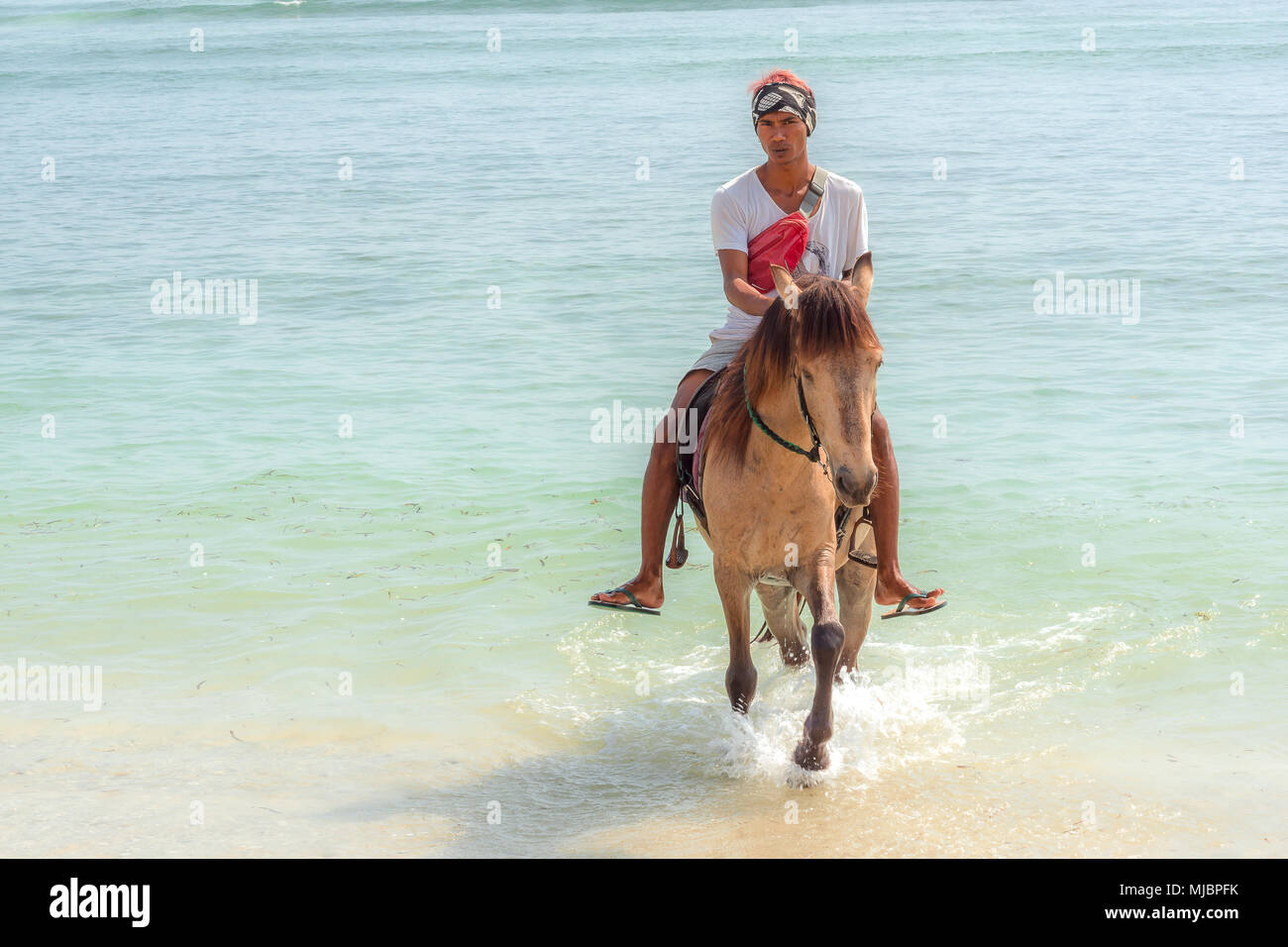 Indonesian man riding a horse in the blue and green water on the beach towards the camera, april 24, 2018, Gili Trawangan, Indonesia Stock Photo