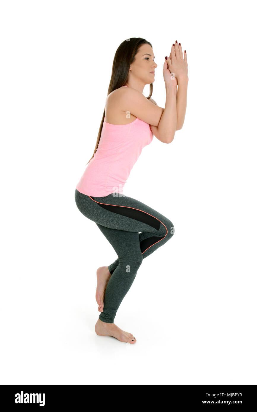 A young white girl performs a yoga asanas. Eagle pose, on sanskrit garudasana. - Stock Image