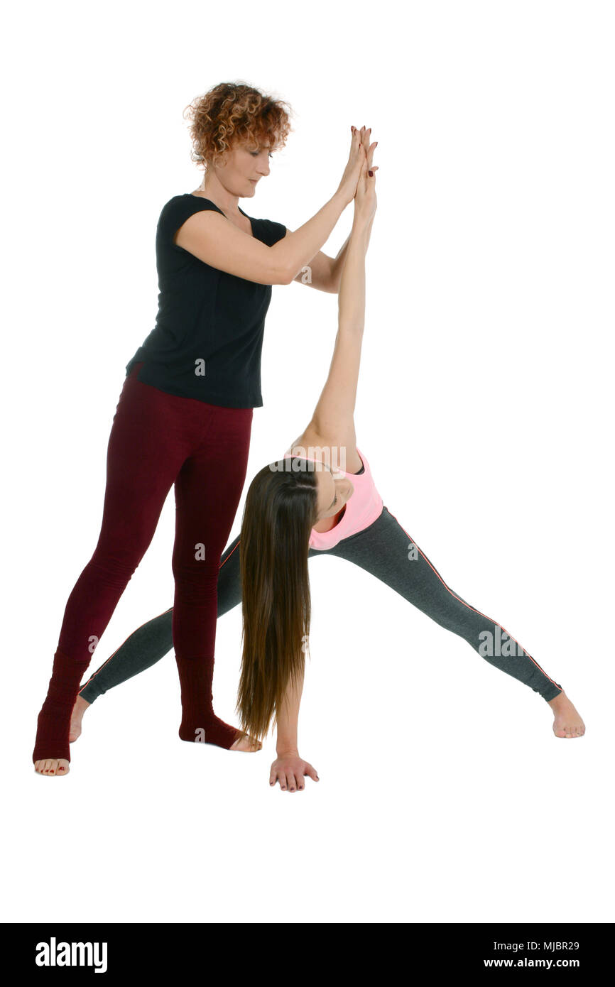 Yoga teacher shows how to put a young girl in the Yoga position Wide-Legged Forward Bend on sanskrit Prasarita Padottanasana variation with twist Stock Photo