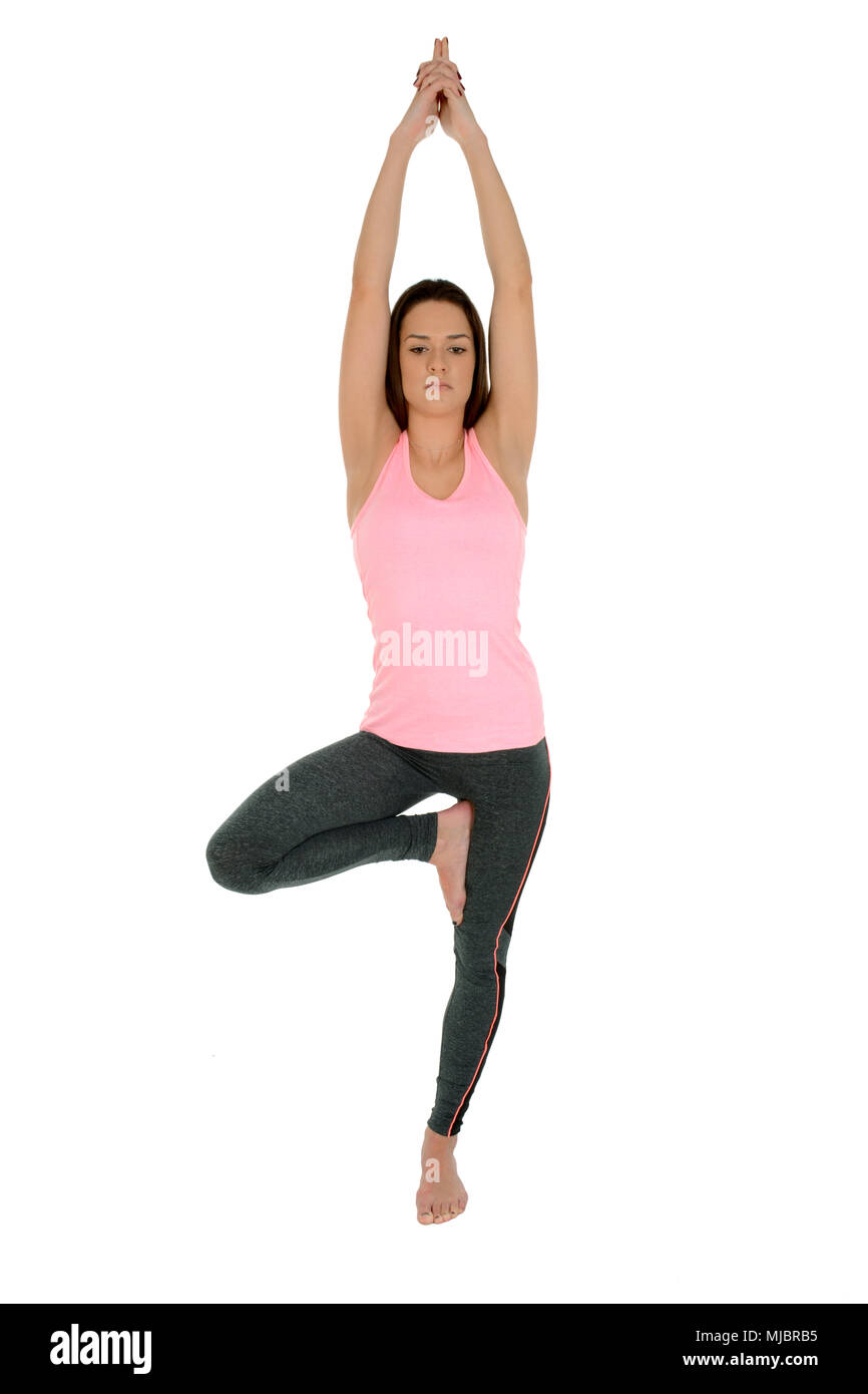 A young white girl performs a yoga asanas Tree Pose,on sanskrit Vrksasana. - Stock Image
