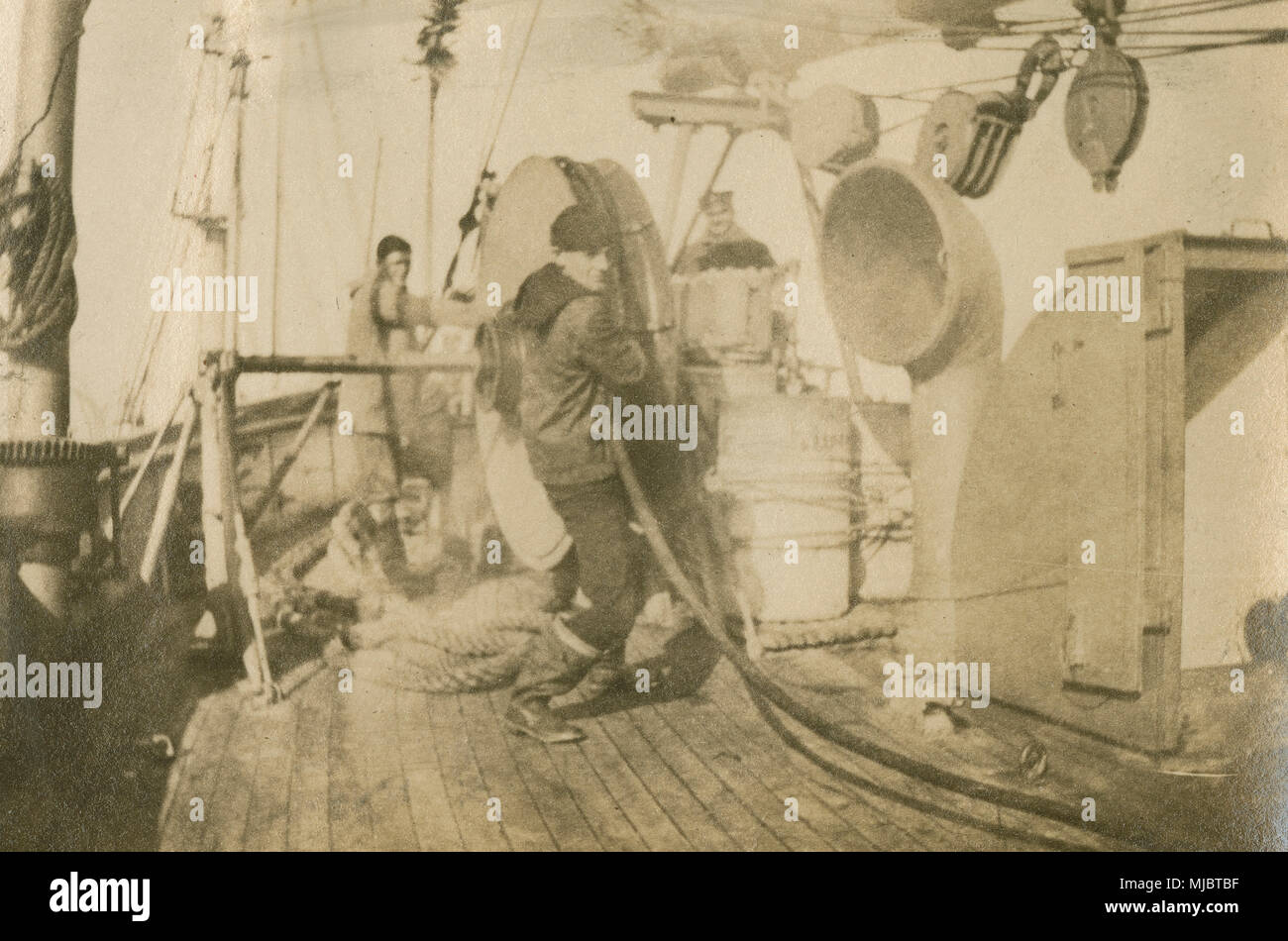 Antique c1922 photograph, view aboard the cable ship USCG Pequot. Forward deck showing cable winch equipment, installed after conversion from an Army mine layer, and companionway stairs to lower crew quarters (at right). SOURCE: ORIGINAL PHOTOGRAPHIC PRINT. - Stock Image