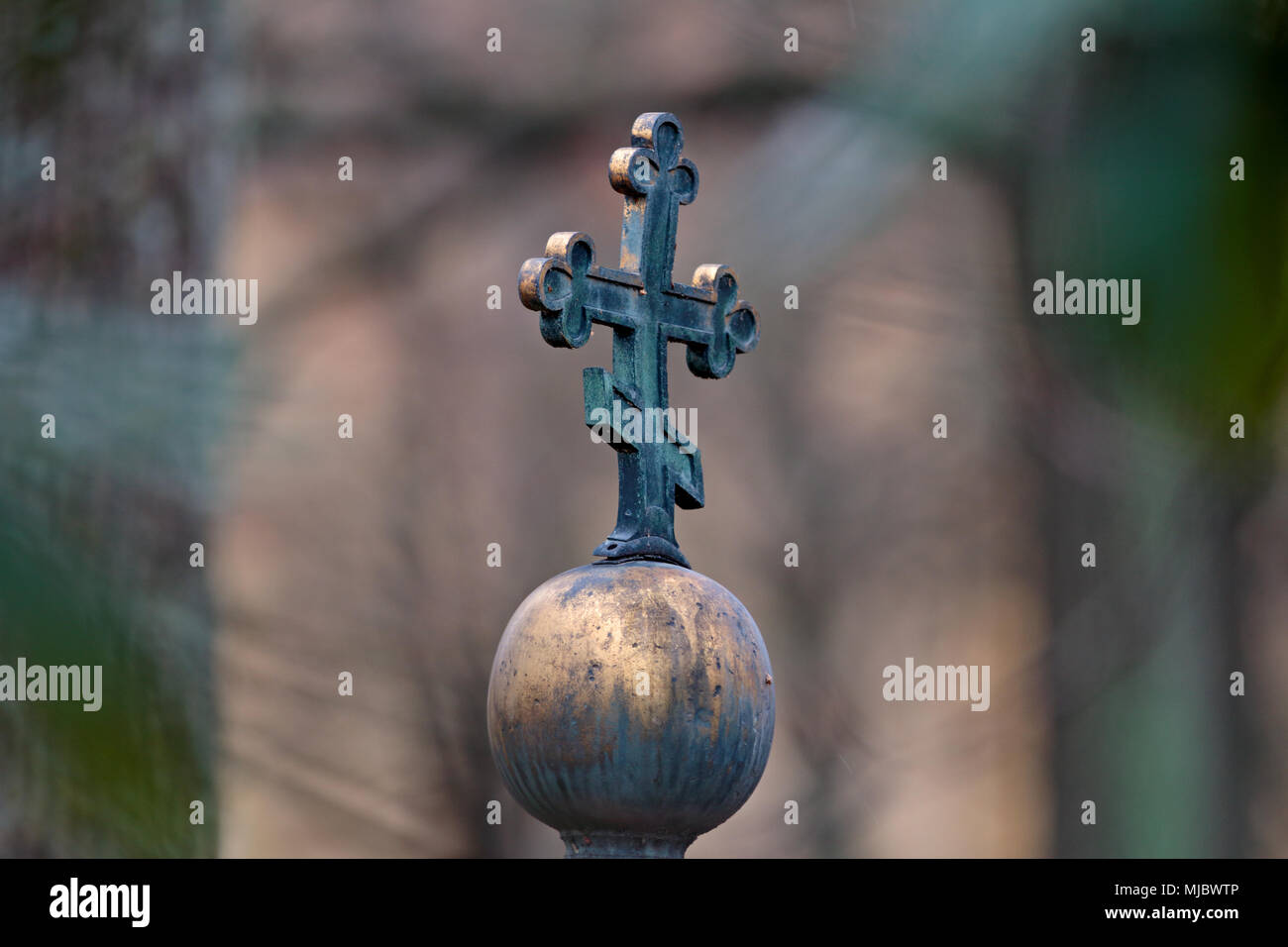 Old religious symbol made of brass in an old graveyard - Stock Image