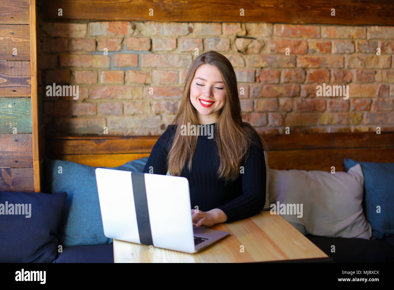 Pretty girl with red lips using laptop at cafe. - Stock Image