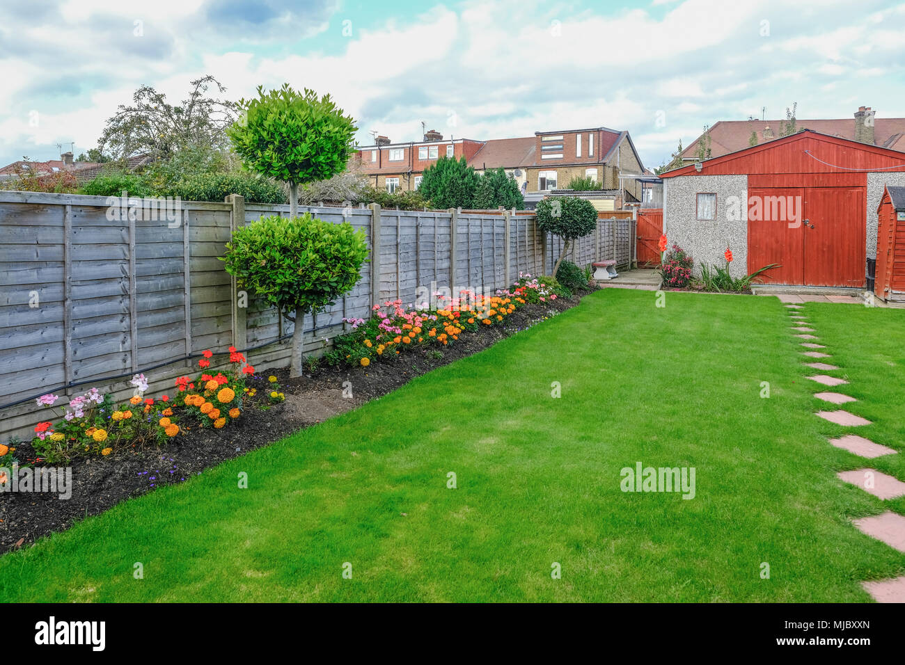 View Of A Typrical Semi Detatched Backgarden With Lawn And Flower