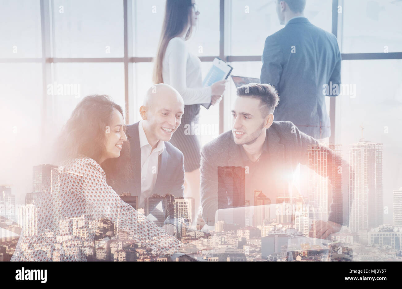 Young team of coworkers making great business discussion in modern coworking office. Teamwork people concept. Double exposition, panorama of modern ci - Stock Image