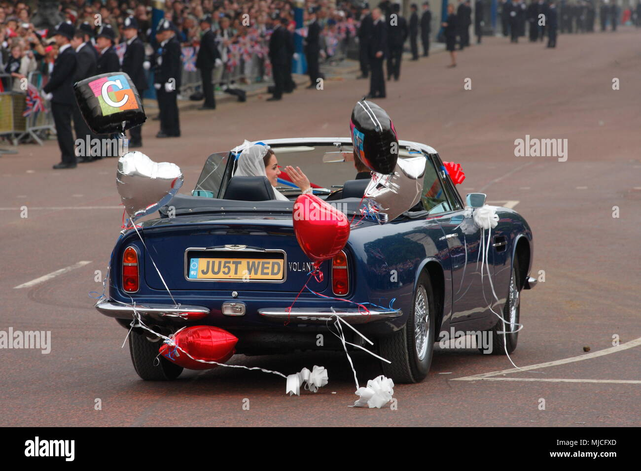 UK - Royal Wedding of Prince William and Kate (Catherine) Middleton - newlyweds William and Kate driving in an open top vintage Aston Martin Volante car along the Mall from  Buckingham Palace 29th April 2011 London UK Stock Photo