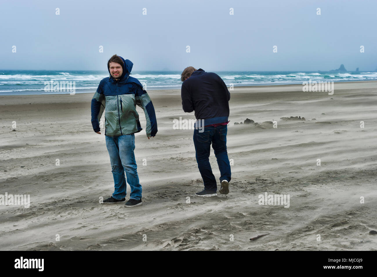 Two brothers brave the windy cold wet weather at Cannon Beach on the