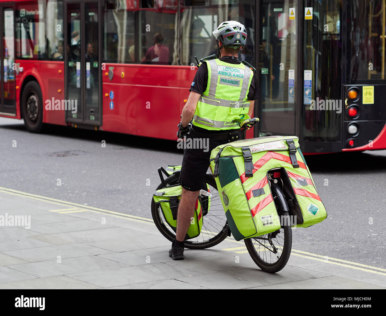 NHS London Ambulance Paramedic on a bicycle in London, UK. 2018. Rear view in front of red London bus. Stock Photo