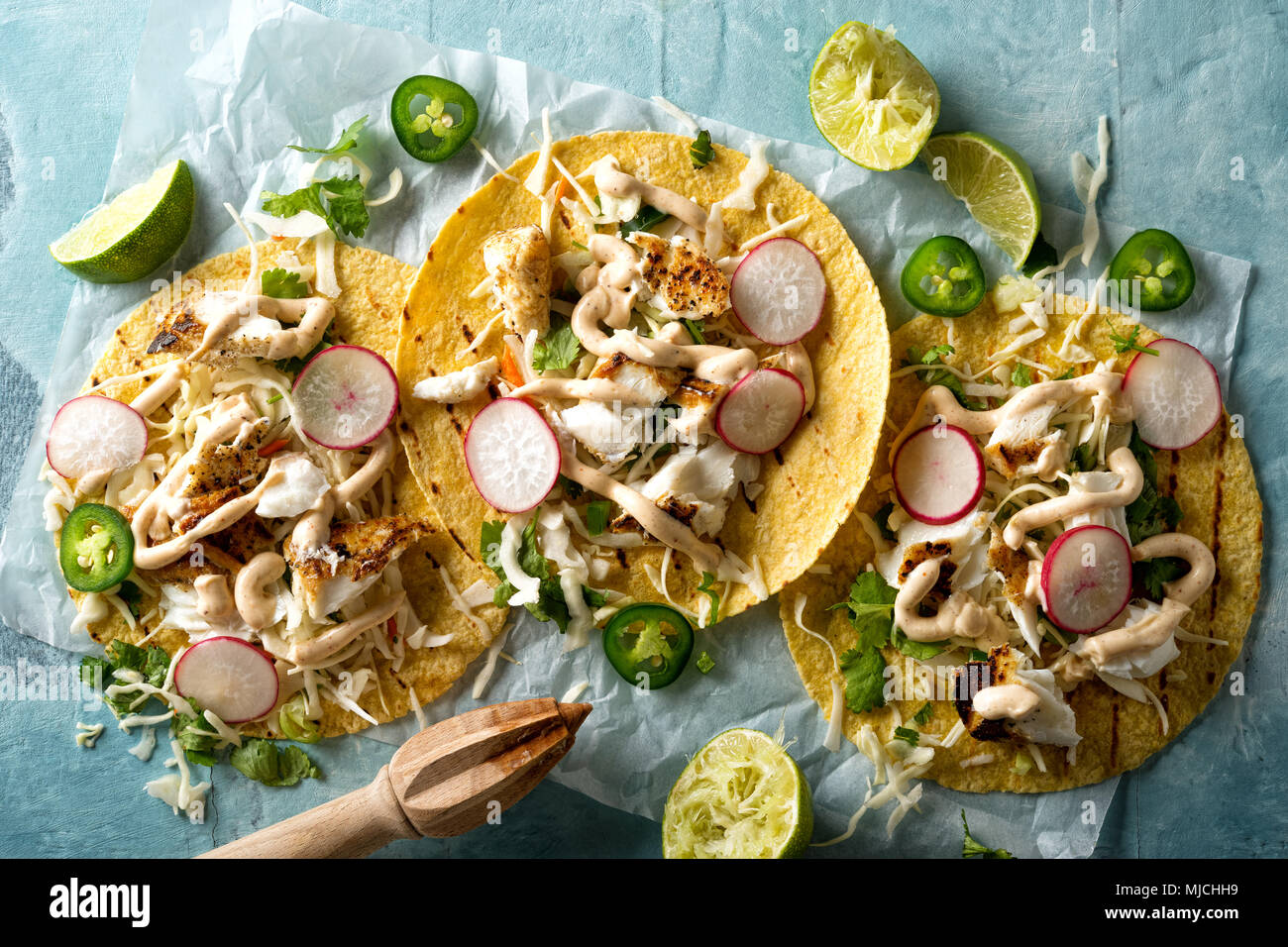 Delicious tacos with grilled fish, cilantro, lime, cabbage, carrot, jalapeno and radish with mexican chili crema sauce. - Stock Image