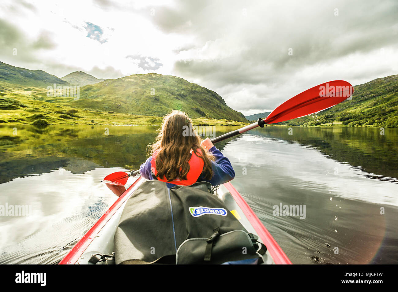 Girl paddles with the kayak on the Loch Eilt, Glenfinnan, Highland, Scotland, - Stock Image