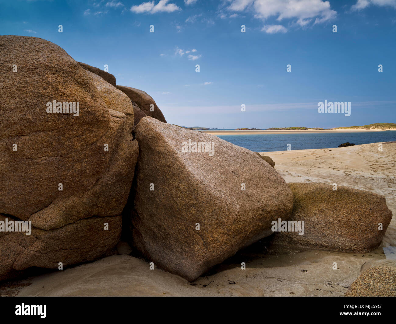 Ireland, Donegal, sandy beach and pink-coloured granite rocks at the Gweedore Bay close Derrybeg - Stock Image
