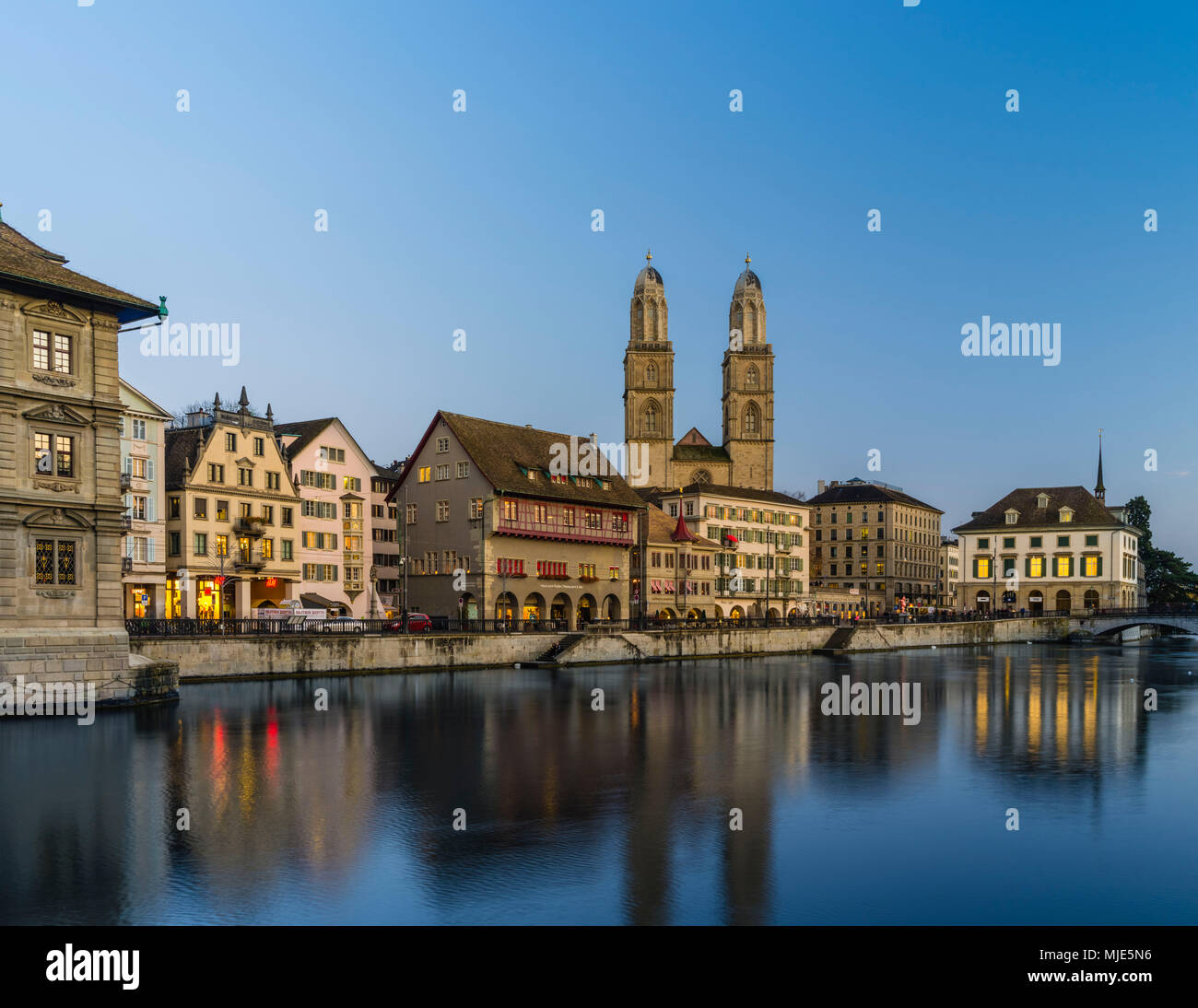 Limmatquai with Grossmuenster, 'Haus zum Rüden' and 'Helmhaus' in the evening at the blue hour - Stock Image