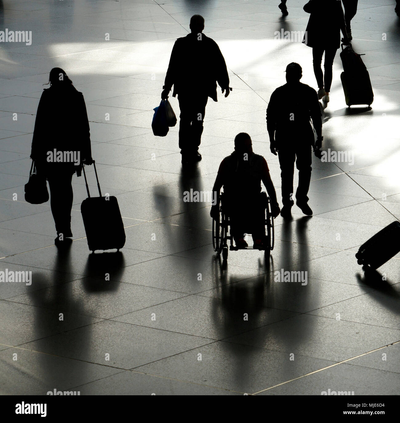 Pedestrians, passers-by, travellers, wheelchair user, movement, silhouette - Stock Image