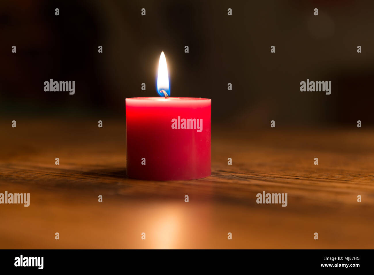red candle on wooden table - Stock Image