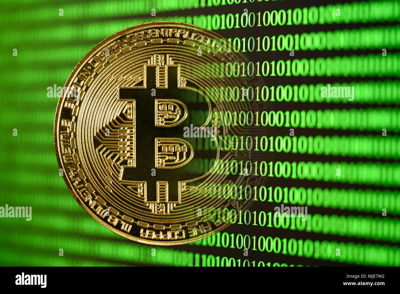 icon digital currency, golden physical coin Bitcoin disappears in digital binary code - Stock Image