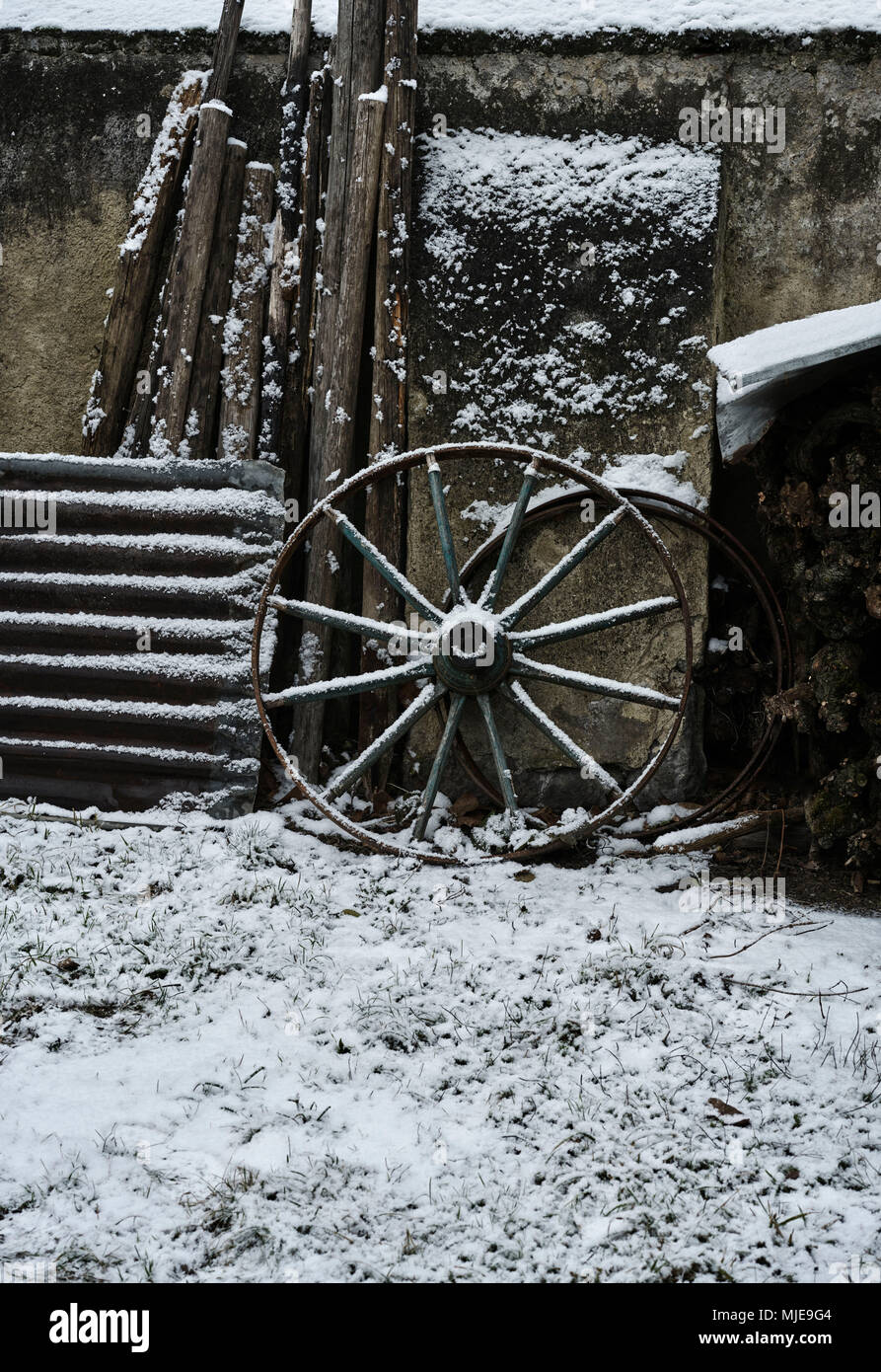 Farm, old cartwheel, corrugated iron and wood on a wall, snow - Stock Image