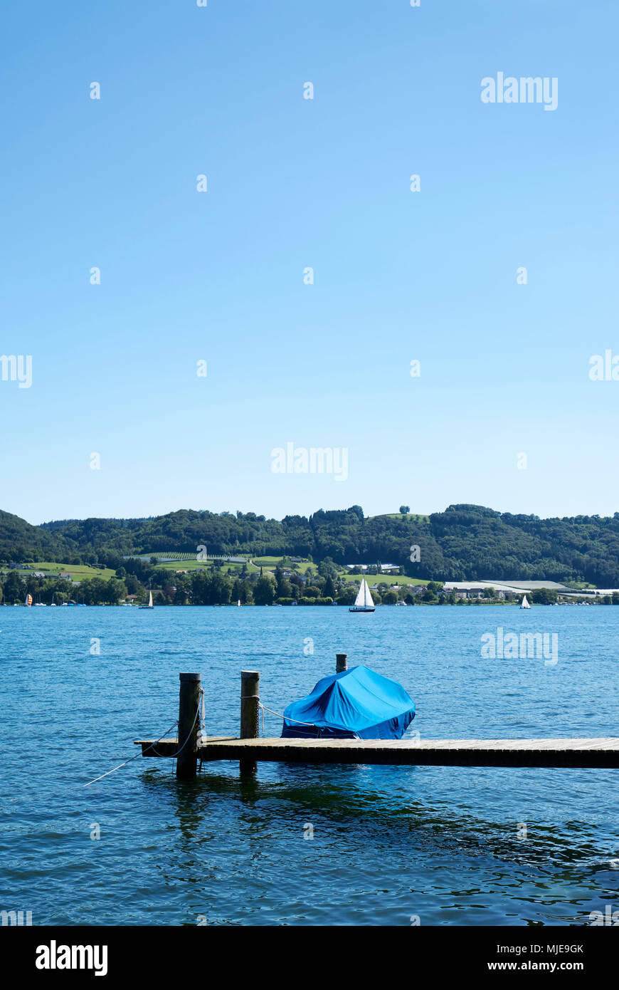 Boat secured on a jetty, view towards the shore, lake in summer - Stock Image
