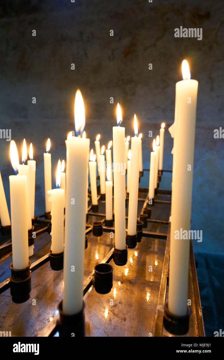 Many white candles are burning in a church, side by side, row, open space - Stock Image
