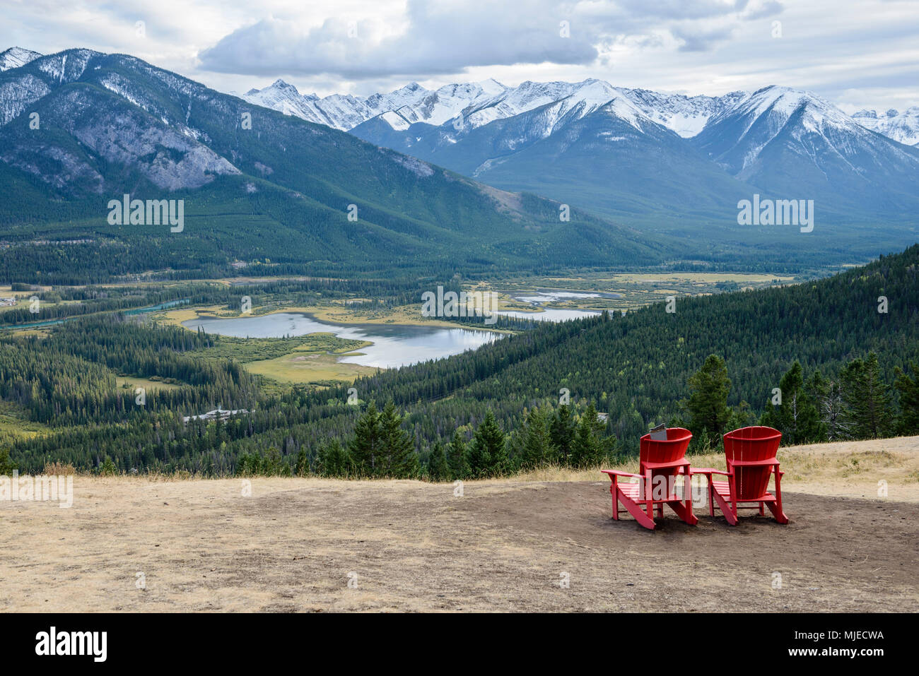 Two red chairs on a flat mountain slope are inviting to sit and enjoy the beautiful view of a green valley near the Banff city, Canada - Stock Image