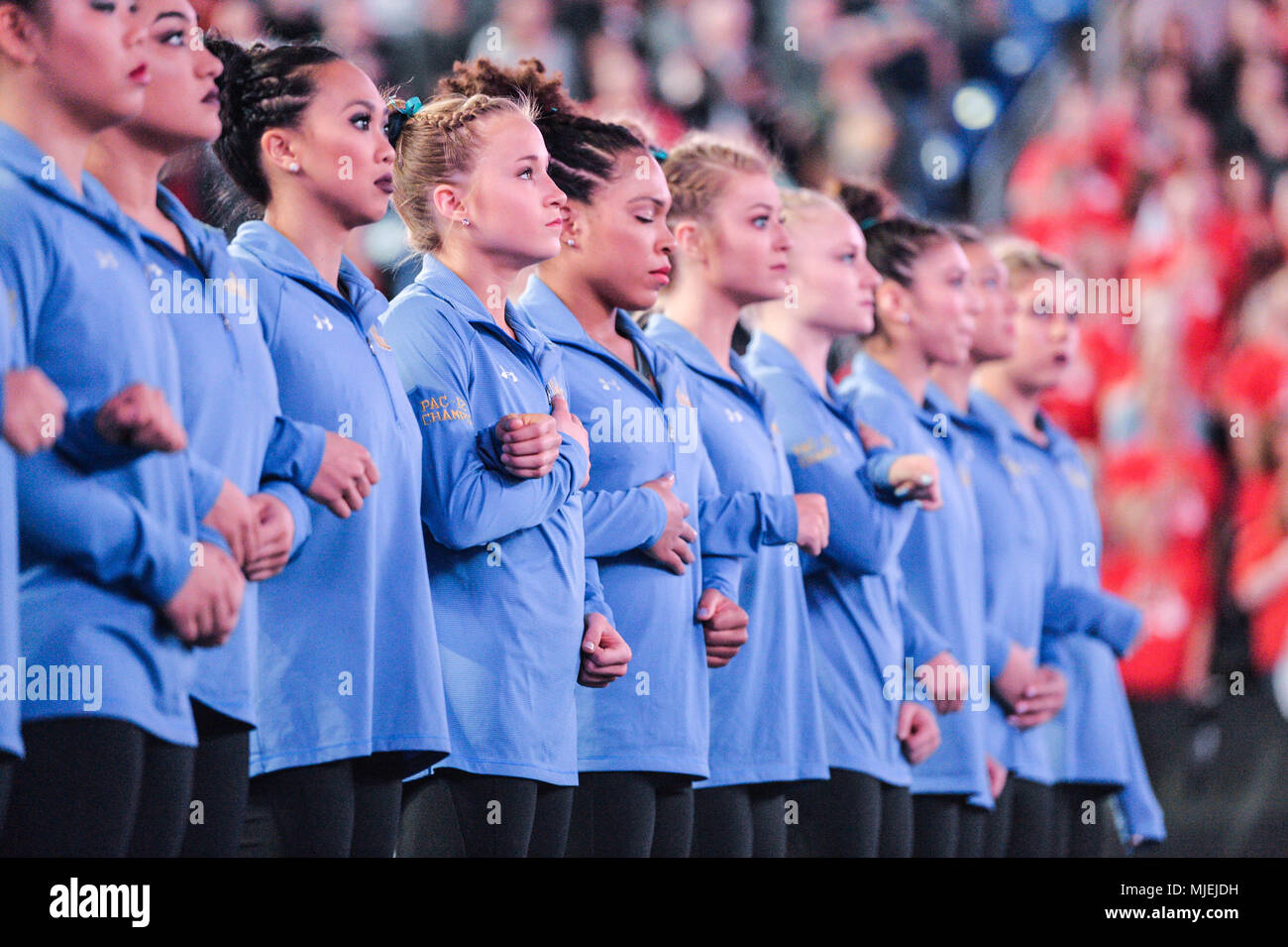 St. Louis, Missouri, USA. 21st Apr, 2018. The UCLA gymnastics team links arms during the national anthem before the meet held at Chaifetz Arena in St. Louis, Missouri. Credit: Amy Sanderson/ZUMA Wire/Alamy Live News - Stock Image