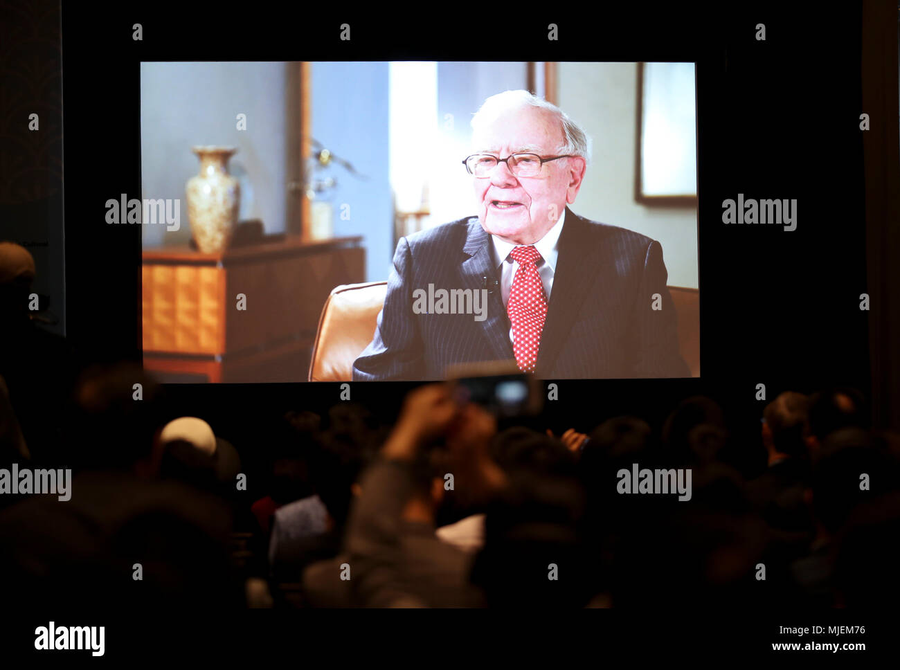 Omaha. 4th May, 2018. Participants watch a video of an interview of U.S. billionaire investor Warren Buffett in Omaha, the United States, May 4, 2018, one day prior to the Berkshire Hathaway's annual shareholders meeting. Credit: Wang Ying/Xinhua/Alamy Live News - Stock Image