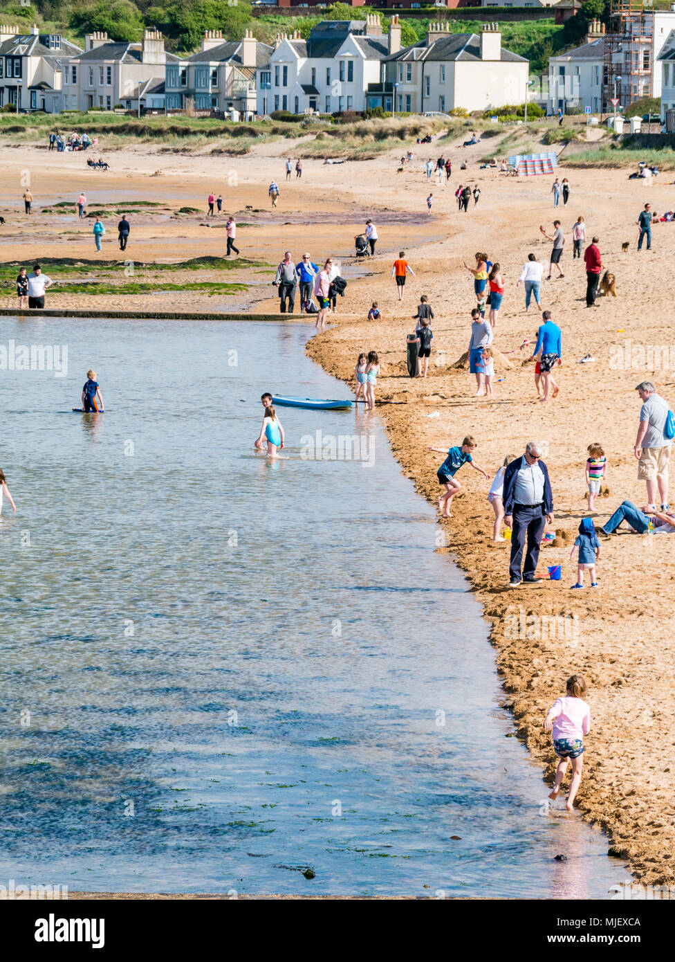 North Berwick, East Lothian, Scotland, United Kingdom, 5th May 2018.  The sun shines on the seaside town.  It is very busy with people enjoying outdoor activities on the bank holiday weekend. The beach at Milsey Bay is crowded with families, and children play in the tidal bath pool - Stock Image