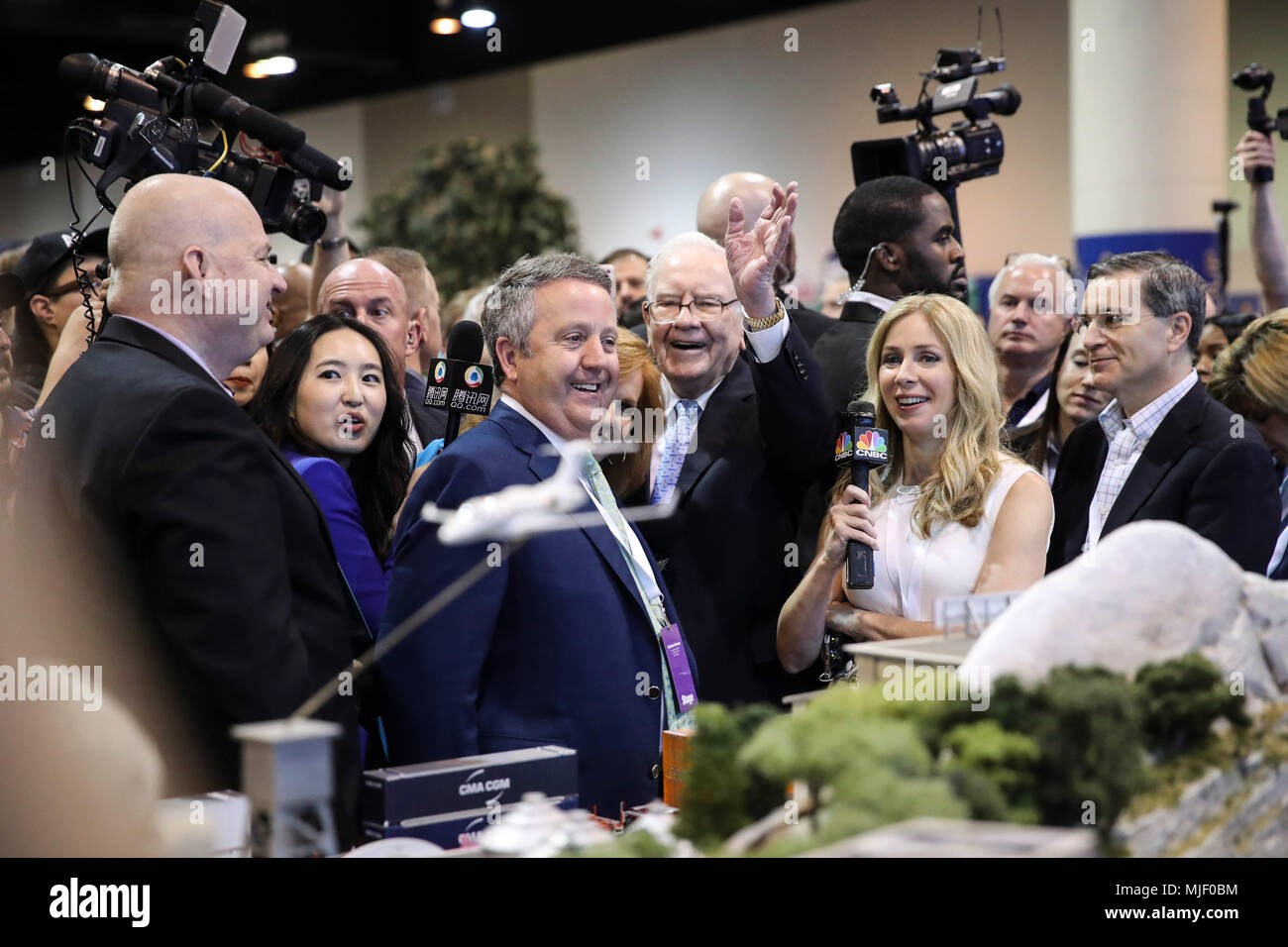 Omaha, USA. 5th May, 2018. U.S. billionaire investor Warren Buffett (C), chairman and CEO of Berkshire Hathaway, greets people as he visits an exhibition on his invested companies before the Berkshire Hathaway's annual shareholders meeting in Omaha, Nebraska, the United States, on May 5, 2018. Berkshire Hathaway held its 2018 shareholders meeting on Saturday, attended by tens of thousands of people from all over the world. Credit: Wang Ying/Xinhua/Alamy Live News - Stock Image