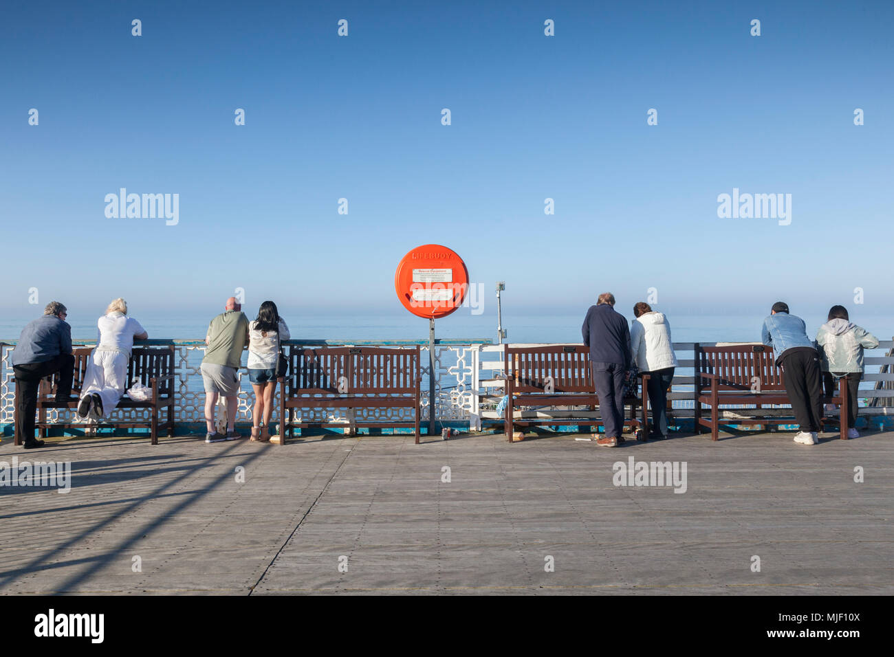 Llandudno, North Wales, UK, 5 May 2018.  Couples looking out to sea from the end of the pier on May Day weekend in glorious sunshine. - Stock Image