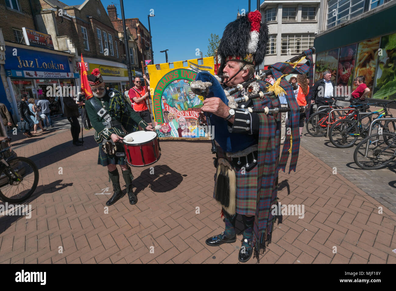 London, UK. 5th March 2018. A drummer and a piper lead trade unionists and other socialists on their march through Croydon town centre to a rally at Ruskin House in celebration of May Day, International Workers Day which is celebrated internationally on May 1st.  Unfortunately May Day is not a Bank Holiday in the UK. The marchers were lead through the main shopping street by a piper and drummer in full Scots dress, attracting the attention of shoppers and others on the busy street. I left the march before it reached Ruskin House where there was to be a rally with speakers including Ted Knight. - Stock Image