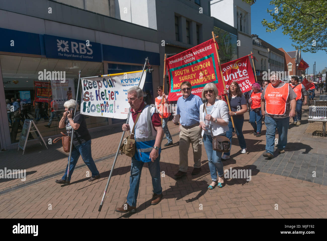 London, UK. 5th March 2018. Trade unionists and other socialists with posters and banners on the march through Croydon town centre to a rally at Ruskin House in celebration of May Day, International Workers Day which is celebrated internationally on May 1st.  Unfortunately May Day is not a Bank Holiday in the UK. The marchers were lead through the main shopping street by a piper and drummer in full Scots dress, attracting the attention of shoppers and others on the busy street. I left the march before it reached Ruskin House where there was to be a rally with speakers including Ted Knight. Pet - Stock Image