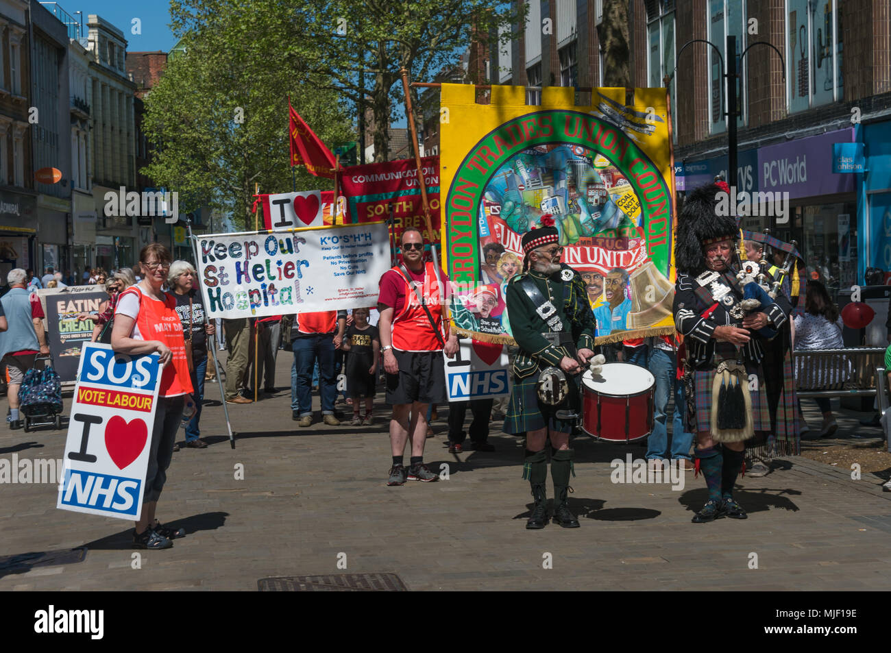 ondon, UK. 5th March 2018. A drummer and a piper lead trade unionists and other socialists on their march through Croydon town centre to a rally at Ruskin House in celebration of May Day, International Workers Day which is celebrated internationally on May 1st.  Unfortunately May Day is not a Bank Holiday in the UK. The marchers were lead through the main shopping street by a piper and drummer in full Scots dress, attracting the attention of shoppers and others on the busy street. I left the march before it reached Ruskin House where there was to be a rally with speakers including Ted Knight. Stock Photo