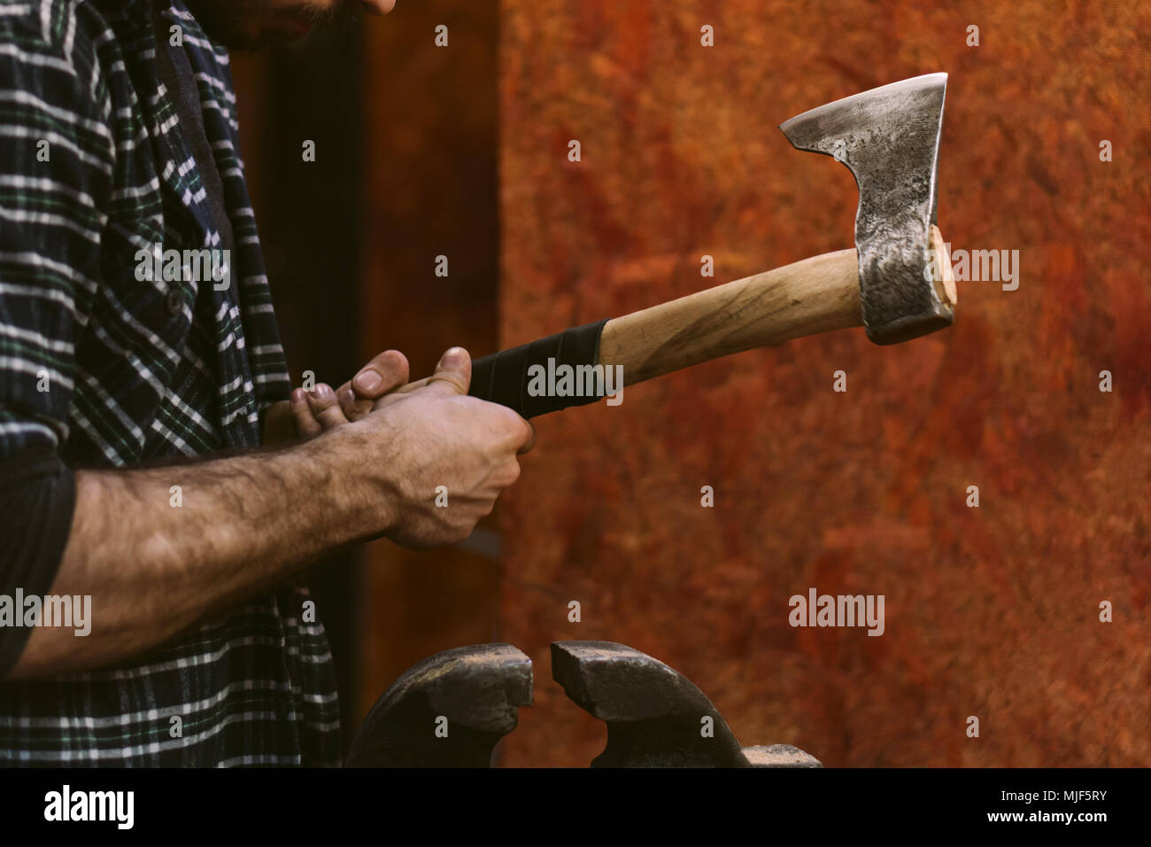 Man working in carpentry workshop. He makes leather winding on wooden ax handle. Men at work. Hand work. - Stock Image