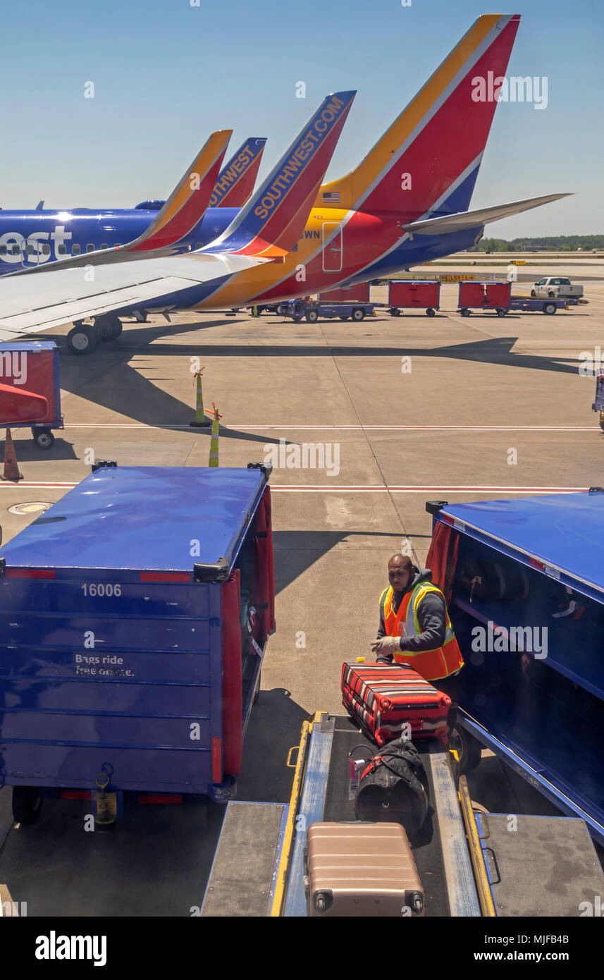 Atlanta, Georgia - A baggage handler unloads a Southwest Airlines jet at the Atlanta airport. - Stock Image