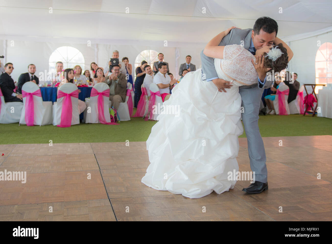 Bride and groom dancing and kissing each other at the reception in a latin-caucasian wedding - Stock Image