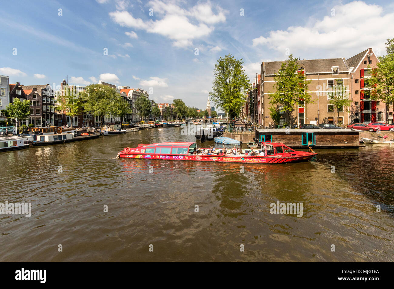 Boats on the 17th Century canal ring taking goods and tourist site seeing round the city of Amsterdam Netherlands - Stock Image